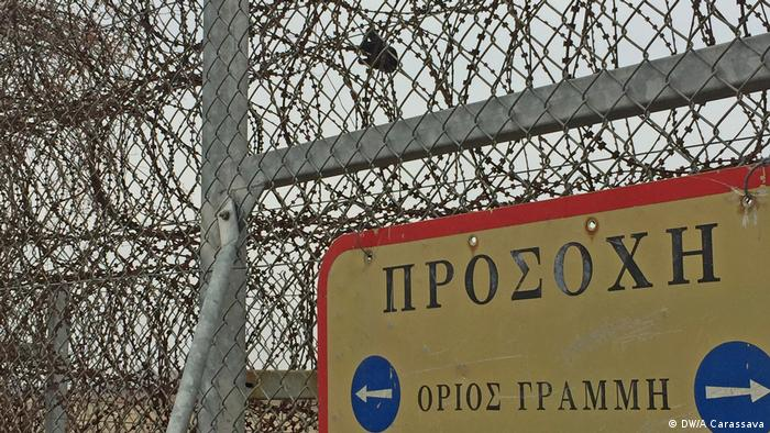 A refugee's torn glove hangs from the fence that divides Greece and Turkey next to a sign that reads: 'Beware: Greek-Turkish borderline'