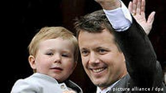 Denmark's Crown Prince Frederik waves to the crowd with his first-born child and heir to the throne, Prince Christian, in his arms