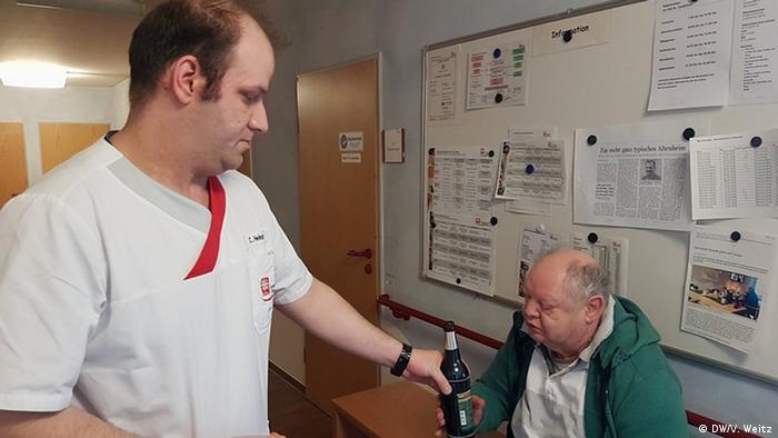 Заведующий отделением Кристоф Хайнце выдает постояльцу бутылку пива