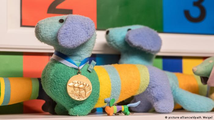 A colorful stripped stuffed animal dachshund wears a gold medal around its neck picture-alliance/dpa/A. Weigel)