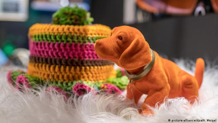 A bobble head dachshund sits next to a roll of toilet paper that has a crocheted hat around it (picture-alliance/dpa/A. Weigel)