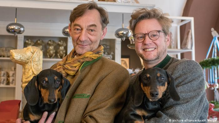 Two men wearing traditional Bavarian jackets carry their pet dachshunds in their arms (picture-alliance/dpa/A. Weigel)