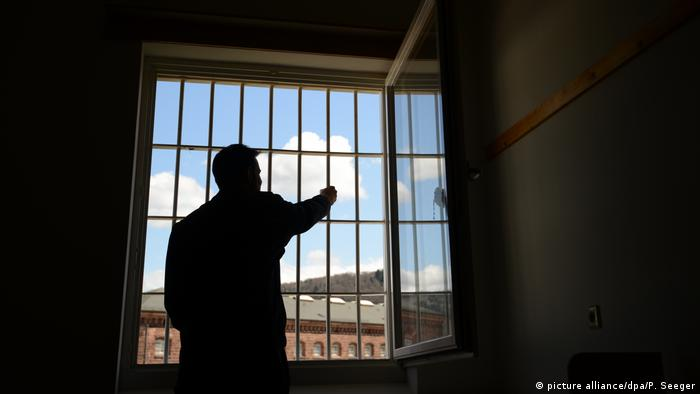 A prisoner staring out of a prison window