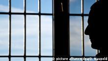 ARCHIV- Ein Gefängnisinsasse sitzt am 04.03.2015 in der Justizvollzugsanstalt in Heilbronn (Baden-Württemberg) vor einem vergitterten Fenster. (zu dpa «Neue Runde im Rechtsstreit um Schmerzensgeld für Justizopfer» vom 18.10.2017) Foto: Daniel Naupold/dpa +++(c) dpa - Bildfunk+++   Verwendung weltweit