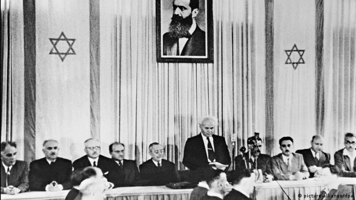 Ben-Gurion announces Israel's independence from a table where lots of other people sit (picture-alliance/dpa)