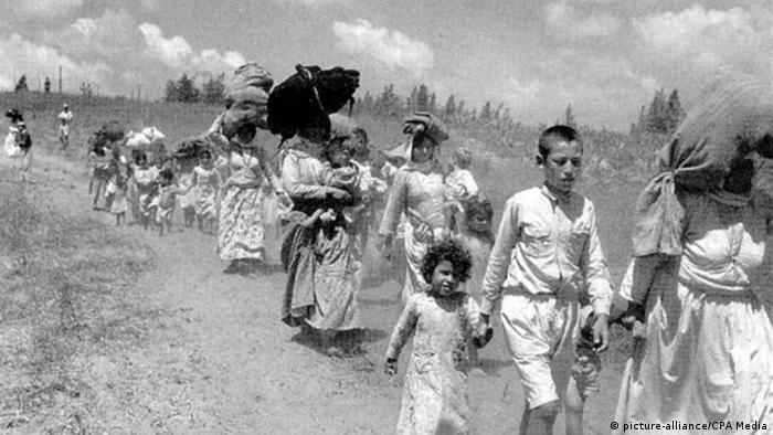 Women and children walk down a dusty road as they leave Palestine (picture-alliance/CPA Media)