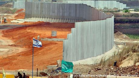 A concrete wall under construction winds its way along a base in the desert while an Israeli flag waves in front (picture-alliance/dpa/dpaweb/S. Nackstrand)