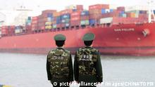 Chinese police watch over a shipping container(picture alliance/AP Images/CHINATOPIX)