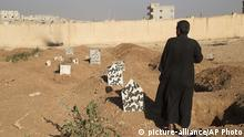 This picture released on Wednesday, Oct. 26, 2016 by the New York-based group Human Rights Watch, shows a family member stands next to the graves of three children who were killed when an explosive device planted by Islamic State group in a school detonated on September 27 in Manbij, Syria. Homemade landmines planted by the Islamic State group have killed and injured hundreds of civilians, including dozens of children, in the town of Manbij in northern Syria, Human Rights Watch says. (Ole Solvang, Human Rights Watch via AP) |