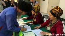 A man receives his ballot during a parliamentary election in Ashgabat, Turkmenistan March 25, 2018. REUTERS/Marat Gurt