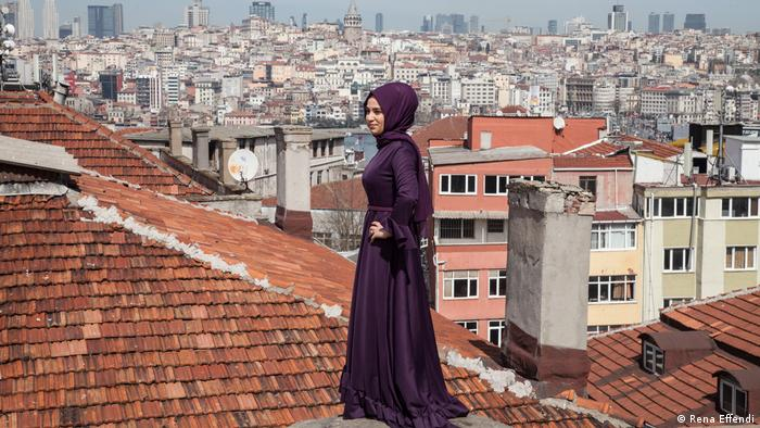 A young woman poses on a roof overlooking Istanbul (Rena Effendi)