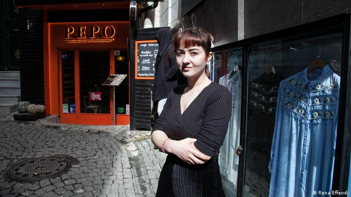 A young woman stands outside a shop in Istanbul's Galata neighborhood Rena Effendi)