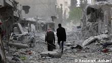March 24, 2018. Men walk through debris in the center of Afrin, Syria March 24, 2018. REUTERS/Khalil Ashawi