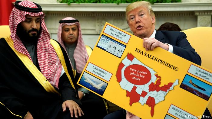 U.S. President Donald Trump holds a chart depicting military hardware sales as he welcomes Saudi Arabia's Crown Prince Mohammed bin Salman in the Oval Office at the White House in Washington.