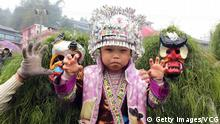 LIUZHOU, CHINA - FEBRUARY 24: Young men dressed as Manggao (God of Mountain in Miao nationality) pose with a girl during the Manggao Festival at Rong'an County on February 24, 2018 in Liuzhou, Guangxi Zhuang Autonomous Region of China. As a traditional custom, young men of Miao nationality wear masks with clothes made of manggao vines to act as Manggao (God of Mountain in Miao nationality) during the Manggao Festival. They catch, touch and shake hands with people and stain their faces to bless them. (Photo by Wei Rongjun/VCG/Getty Images)