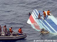 Divers recover a part of the A330's tail, bearing the Air France logo. A small dinghy floats nearby, coordinating the recovery.
