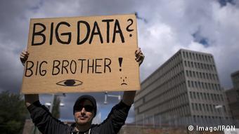 Парень держит в руках плакат с надписью Big Data? Big brother!