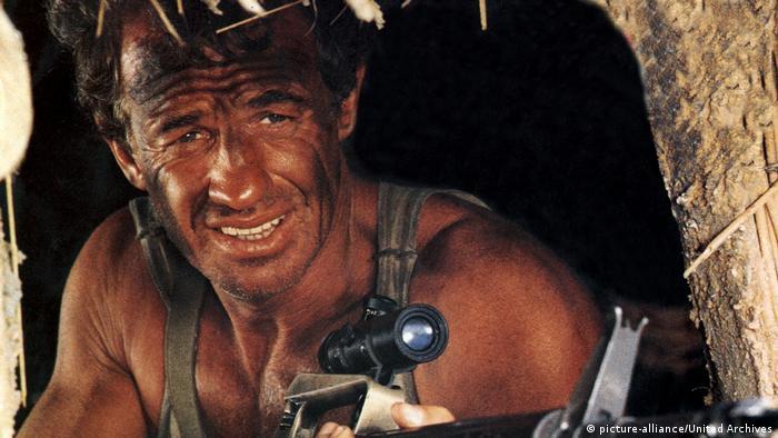 Jean-Paul Belmondo mit Waffe und geschwärztem Gesicht in Der Profi