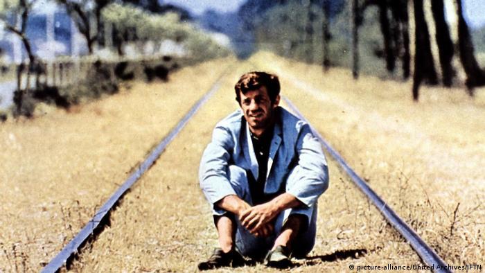 Jean-Paul Belmondo sitzt in der hellen Provence-Sonne auf einem einsamen Bahngleis. (picture-alliance/United Archives/IFTN)