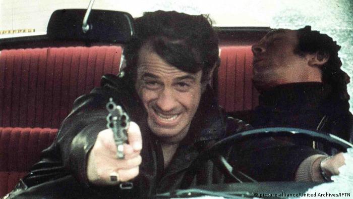 Jean-Paul Belmondo in einer rasanten Fahrszene, sitzt am Lenker und zielt gleichzeitig mit einer Waffe. Auf der Rückbank ein lebloser Mann. (picture-alliance/United Archives/IFTN)