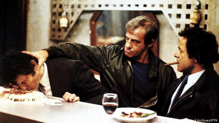 Jean-Paul Belmondo drückt den Kopf seines Nachbarn an der Theke in einen Teller Spaghetti mit Bolognese. Rechts von ihm sitzt ein Mann mit Zigarre im Mund und guckt zu. (picture-alliance/United Archives/IFTN)