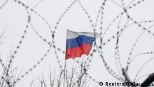 Russische Flagge hinter Stacheldraht