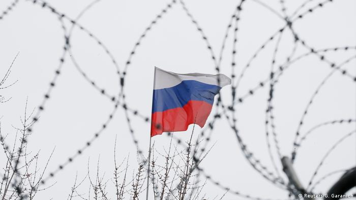 A Russian flag waves behind barbed wire