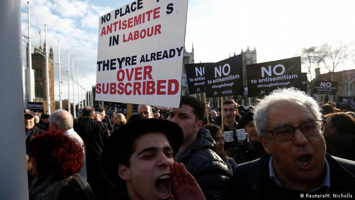 Protesters hold placards and flags during a demonstration, organised by the British Board of Jewish Deputies