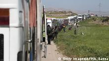 A convoy transporting Syrian civilians and rebel fighters evacuated from Eastern Ghouta waits in a government-held area prior to entering the village of Qalaat al-Madiq, some 45 kilometres northwest of the central city of Hama, on March 26, 2018, as evacuations from the opposition enclave continued following a deal that was announced earlier in the week. / AFP PHOTO / ABDULMONAM EASSA (Photo credit should read ABDULMONAM EASSA/AFP/Getty Images)