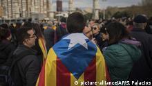 27.03.2018, Spanien, Barcelona: Ein in einer Unabhängigkeitsflagge gehülter Demonstrant protestiert mit anderen Teilnehmern. Die Kundgebungen fanden zu Unterstützung inhaftierter katalanische Politiker, sowie den aktuell inhaftierten ehemaligen katalanischen Präsident Puigdemont statt. Foto: Santi Palacios/AP/dpa +++(c) dpa - Bildfunk+++  