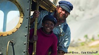 Filmszene aus Jim Knopf und Lukas der Lokomotivführer. Die Schauspieler schauen aus der Tür ihrer Lok Emma und lächeln in die Kamera (Bild: Warner Bros., Ilze Kitshoff)