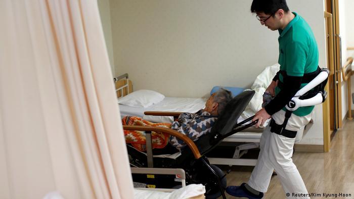 Cuidador transporta a un anciano en Japón con la ayuda de un traje robot.