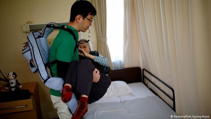 Un traje de músculos ayuda a un cuidador a levantar a una anciana.