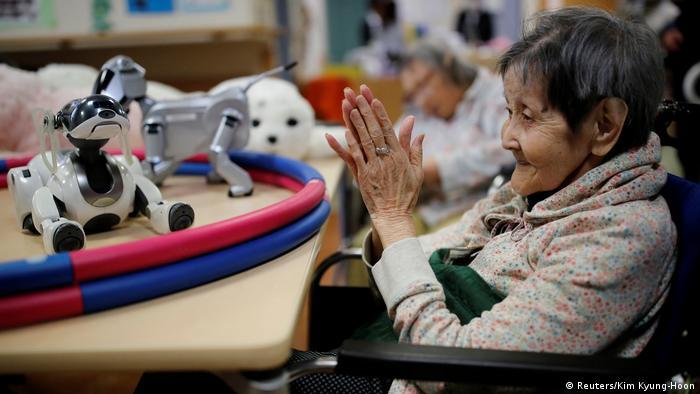 Eine Seniorin klatscht in die Hände. Vor ihr liegt ein Roboter-Hund. (Foto: Reuters)