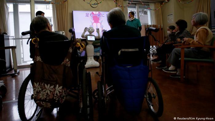 Ein menschenartiger Roboter hebt seine Hände, um Senioren in einem Altenheim in Tokio eine Trainingsstunde zu geben. (Foto: Reuters)