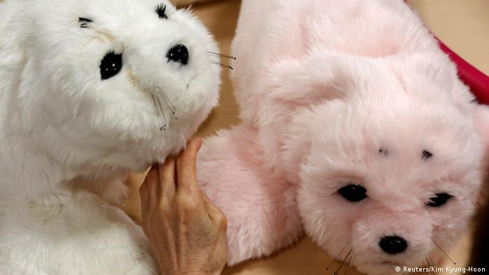 Zwei Roboter-Robben in weiß und rosa werden gestreichelt. (Foto: Reuters)
