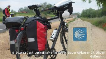 A bicycle with paniers stands behind a scallop waymark for the Way of Saint James (Evangelisch-Lutherische Kirche in Bayern/Pfarrer Dr. Oliver Gußmann)