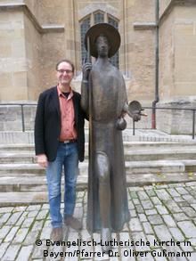 Gussman stands next to a statue of Saint James in Rothenburg(Evangelisch-Lutherische Kirche in Bayern/Pfarrer Dr. Oliver Gußmann)