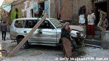 A Yemeni armed man inspects the wreckage of a car at the scene of a bomb explosion that targeted the house of a member of the Shiite Huthi movement on December 23, 2014 in the capital Sanaa. Five small bombs hit the centre of the capital, mostly controlled by Shiite militiamen since September, killing at least one of them and wounding two others, a medic said. AFP PHOTO / MOHAMMED HUWAIS (Photo credit should read MOHAMMED HUWAIS/AFP/Getty Images)