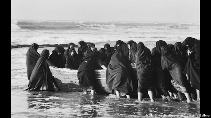 Foto: Frauen im Shador schieben ein Boot ins Meer