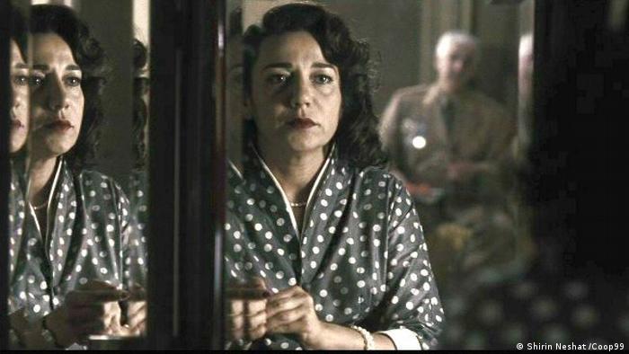 Frau im gepunkteten Kleid spiegelt sich (Shirin Neshat /Coop99)