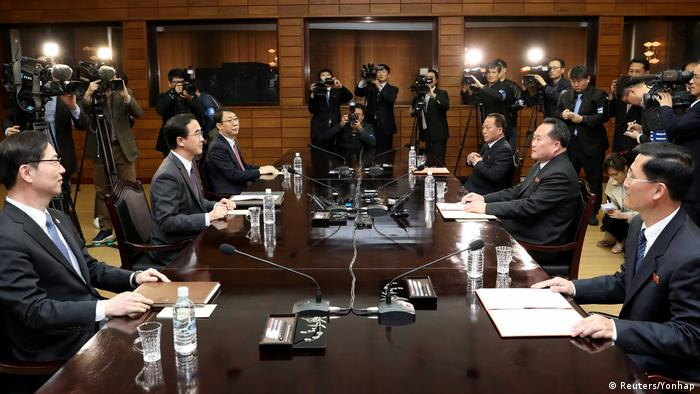 Representatives of the two Koreas sit at a table in Panmunjom