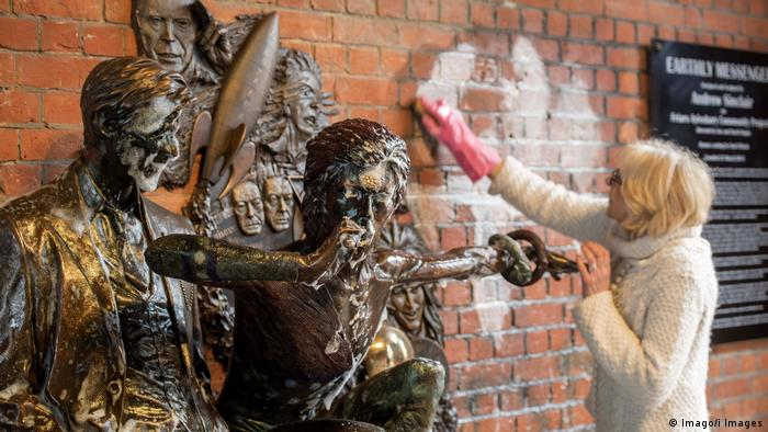 A woman removes graffiti from a wall next to a statue of David Bowie (Imago/i Images)