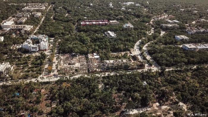 Blick aus der Luft auf Häuser und Straßen, die den Regenwald bei Tulum durchziehen
