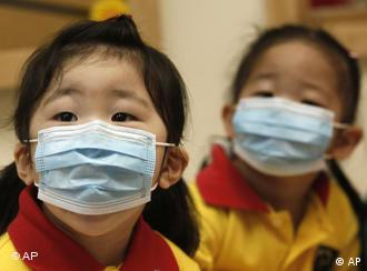 Students wearing mask listen to teacher at a pre-school facility