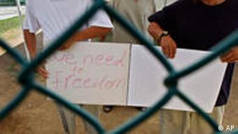 Guantanamo detainees show a home-made note to visiting members of the media, which reads We need to freedom
