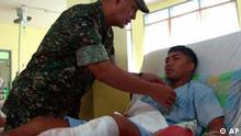 Western Mindanao military chief Marines Lt. Gen. Nelson Allaga pins a medal Thursday March 19, 2009 at a government hospital in Zamboanga city to one of 19 soldiers wounded in clashes with Abu Sayyaf extremists in the southern Philippine island of Sulu. Philippine troops agreed to pull back Thursday from a jungle stronghold of al-Qaida-linked Abu Sayyaf extremists in exchange for a pledge by the militants to free one of three Red Cross hostages, officials said. The move comes after Abu Sayyaf commander Albader Parad threatened to behead the Swiss, Italian and Filipino Red Cross workers he had been holding for more than two months if the military launched a new attack on his group near Indanan township on southern Jolo Island, Sen. Richard Gordon said. (AP Photo/Al Jacinto)