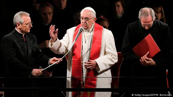 Pope Francis speaks into a microphone during the Via Crucis procession