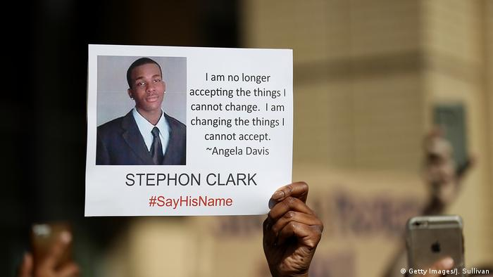 Hand holding up picture of Stephon Clark (Getty Images/J. Sullivan)