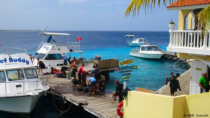 Scuba diving tourists and boats at a dive center